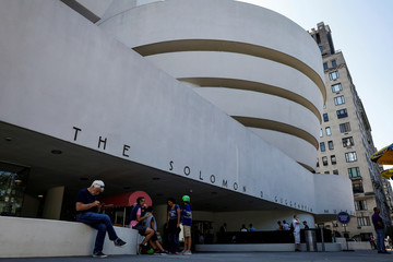 People sit outside The Guggenheim Museum in New York