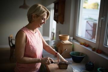 Senior woman cutting bread loaf