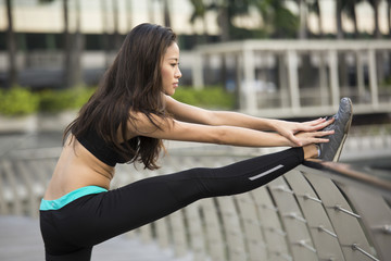 Side view of young asian woman stretching