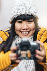 Tourist asian woman using camera in european street.