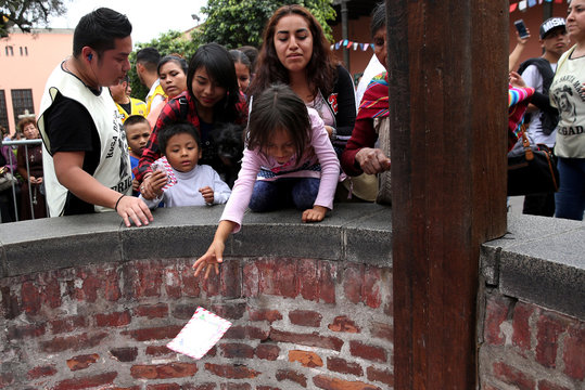 People throw letters into the well of wishes at Saint Rose's Church during celebrations of the anniversary of Santa Rosa de Lima (Saint Rose of Lima) in Lima