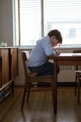 Side view of boy drawing on paper at table