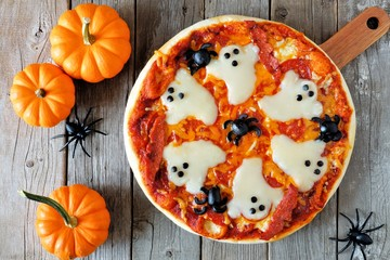 Cadres-photo bureau Pizzeria Halloween pizza with ghosts and spiders, above scene with decor on a rustic wood background