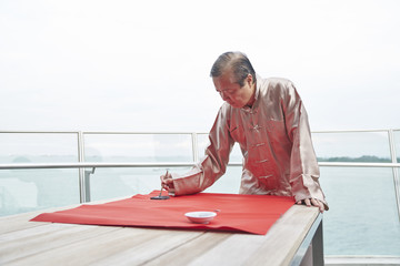 Grandfather writing Chinese calligraphy