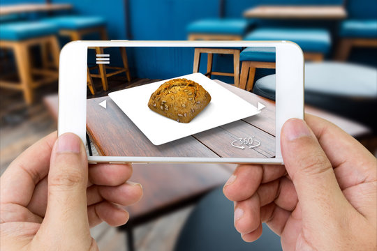 Augmented reality marketing technology concept. Customer hand holding smart phone use AR application to select menu in restaurant. 3d rendering of bread can move 360 degrees for see around object.