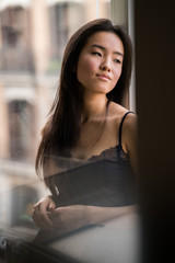 Portrait of beautiful chinese woman indoors next to a window with natural light