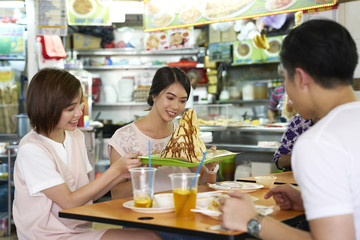Group of friends fascinated with their Tissue Prata in Tekka Centre, Singapore