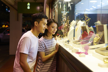 Young couple doing window shopping outside a jewelry store