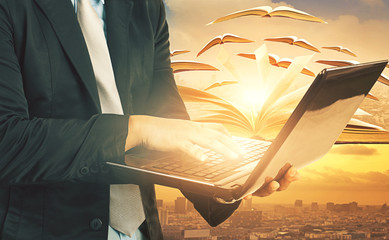 business man laying hand on computer laptop and khonwledge book flying over urban scene