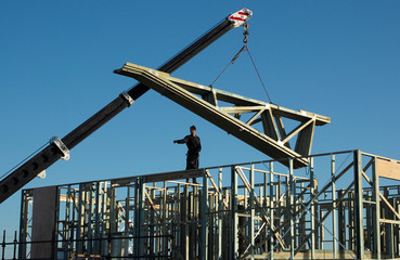 Roof beams are lifted onto the frame of a new house under construction  in Sydney's Greenhills Beach