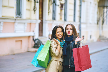 two young women with shopping bags on a city street . Happy shopping