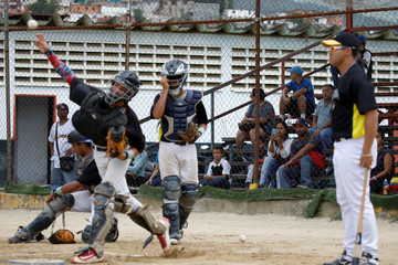 Grey Mejia uses her cellphone to takes pictures to her son Rivaldo Avila and the other players, during a baseball showcase in Caracas