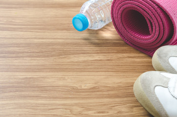 Sport shoes bottle of water, yoga mat on wooden background and copy space for text.
