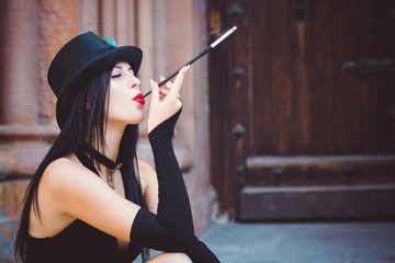 Gorgeous woman smokes mouthpiece in a vintage look of  20s in a black handmade hat with bright make-up, pale skin near the old architecture. Luxury retro style for carnival or Halloween