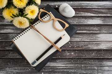 Open notebook, yellow daisy flowers