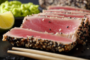 beautiful sliced tuna steak in sesame and wasabi, lime macro. horizontal