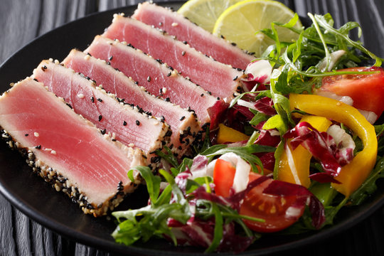 Sliced Steak of tuna in sesame and a salad of fresh vegetables close-up. horizontal