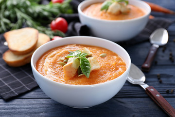 Bowl with delicious carrot soup on wooden table