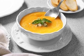 Bowl and spoon with delicious carrot soup on table