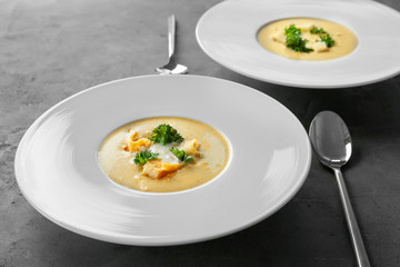 Plates with broccoli cheddar soup on table