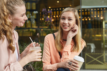 Young adult student people outside in the city drinking coffee and chatting together