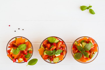 Vegetarian vegetable salad with tomatoes, cucumber, red bell pepper and basil in the glass bowls on the white wooden table, top view.