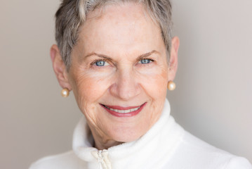 Close up portrait of beautiful older woman with short grey hai, blue eyes and pearl earrings smiling against neutral background (selective focus)