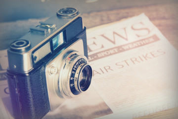 Old vintage retro camera with mocked up newspaper