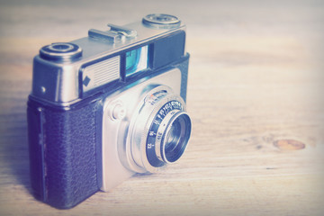 Old vintage retro camera on wooden background