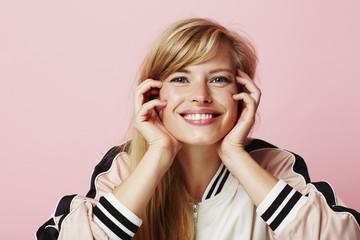 Blue eyed blond in pink varsity jacket, smiling