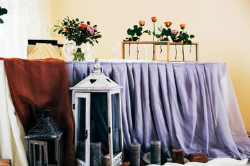 Wooden boxes with roses stand on dinner table covered with blue cloth and decorated with lanterns and candles
