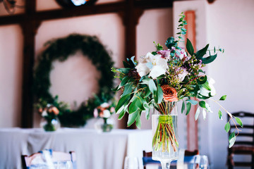 Bouquet of roses and greenery stands in a glass vase in the middle of dinner table