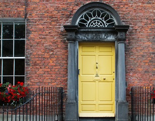 Entrance door of yellow color in Irish town.