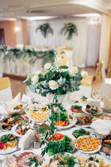 Rich served dinner table decorated with white roses and green branches