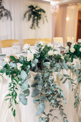 Garland of long green branches and white roses lies on white dinner table
