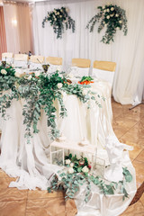 Decorative lanterns with green branches stand on the cloth hanging from dinner table