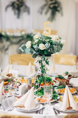Tall vase with bouquet of white roses stands on dinner table