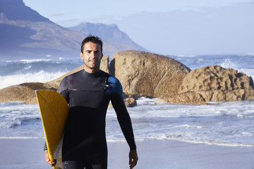 Surfer dude in wetsuit carrying board on beach