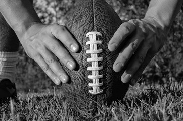 A man holds the ball for American football on the grass. Picture is black and white.