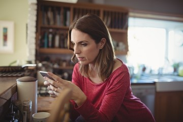 Woman using mobile phone while having coffee in kitchen