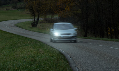 Unfallrisiko PKW mit defektem Licht links fährt bei Dunkelheit über eine Landstraße - Risk of accident Car with defective light on the left drives over a country road in darkness
