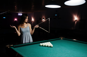 Portrait of a confused woman posing with a triangle by the pool table.