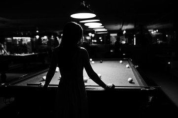 Portrait of an attractive young woman in dress playing pool. Black and white photo.