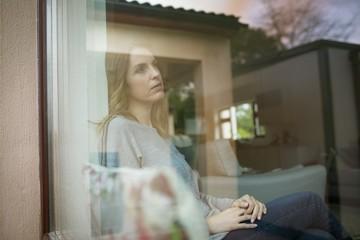 Thoughtful woman seen through glass