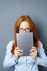 frau versteckt sich hinter ihrem tablet-pc