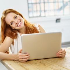 frau sitzt lächelnd am tisch mit ihrem notebook