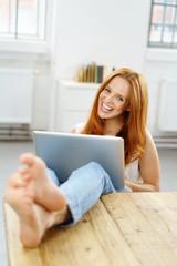 frau sitzt entspannt am tisch und arbeitet am laptop