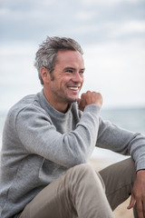 Portrait of a Gray haired man sitting on a rock at the beach