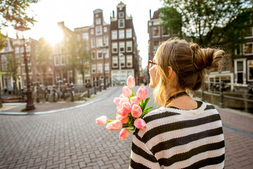 Woman enjoying great view on the buildings holding a bouquet of pink tulips in Amsterdam city