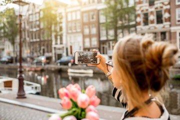 Woman photographing with phone beautiful cityscape during the morning in Amsterdam city